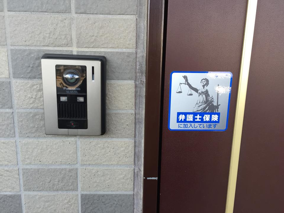 弁護士保険のステッカーが貼られた玄関